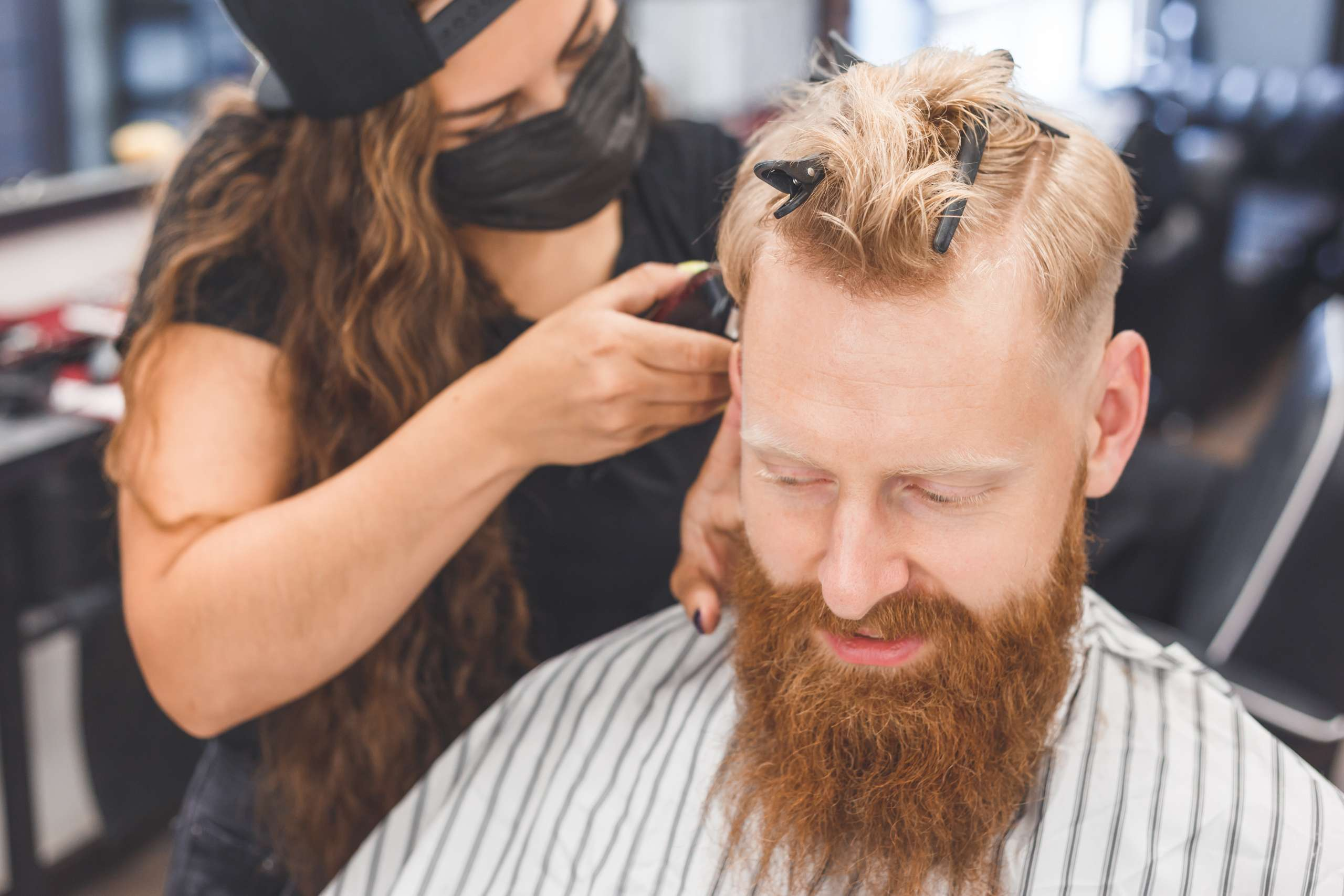 Men's haircut in a barbershop. Hair care. Barber in mask protecting from virus. Haircut in quarantine.